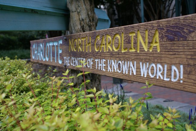 A sign post stating the Charlotte NC is the Center of the Known World!