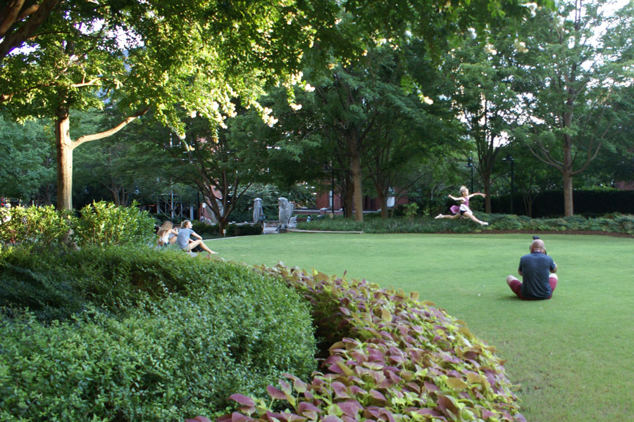Running and jumping on the Green in Uptown Charlotte